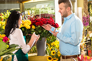 stock image of husband purchasing valentine's day flowers at a florists