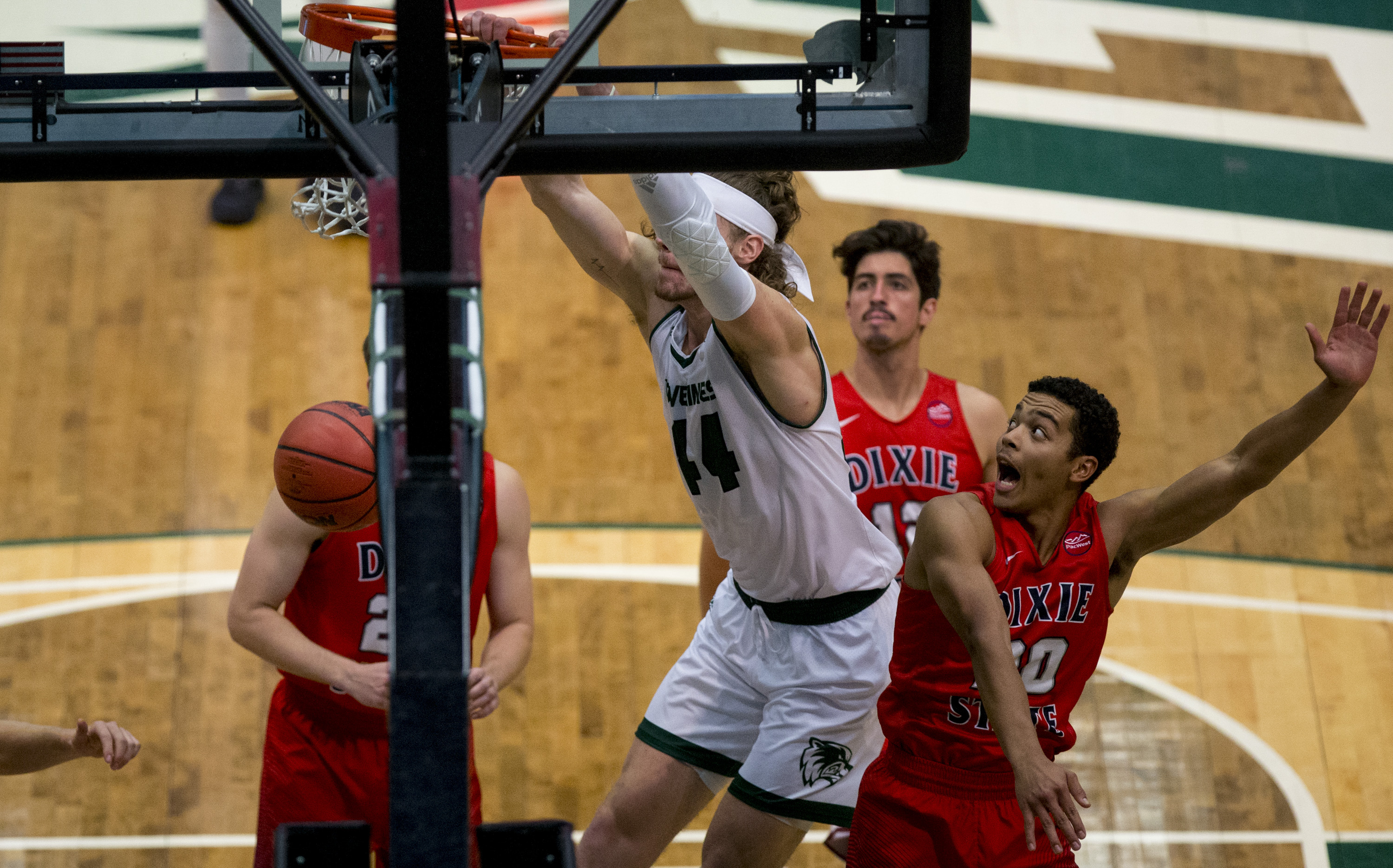 Utah Valley Wolverines center Baylee Steele (44) dunks the ball as Dixie  State Trailblazers guard Andre Wilson (20) reacts during an exhibition game  between ...