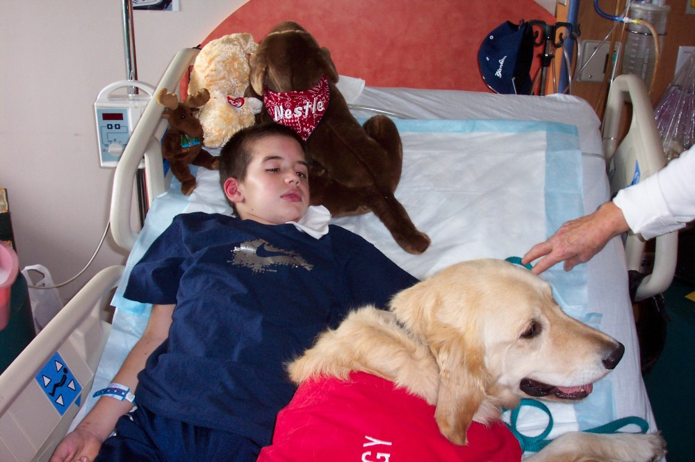 Ryan Boyle in a hospital bed with a therapy dog.