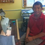 Damber Pulami, originally from Nepal, is a re:loom weaver who uses a sewing machine to finish an item woven from recycled materials. He wove the rug and scarf from Spanx remnants that caught the eye of that company's owner, Sara Blakely.