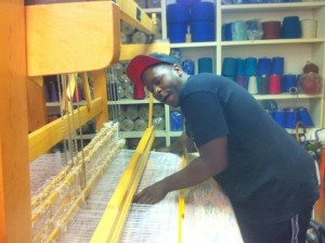Photo of Fred Brown, 29, weaving a rug at re:loom. Two years ago he was living in an abandoned building with his infant son. Now he has an apartment, a job at re:loom and daycare for his 3-year-old.
