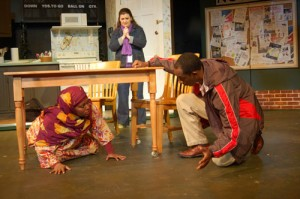 Photo of Asad (Eric J. Little) persuading Nura (Cynthia D. Barker), a Somalian refugee, that the gunfire next door is only a loud video game. Looking on is Sasha (Marcie Millard), a relief agency worker. Credit: Third Country, 2013, Horizon Theatre Company.