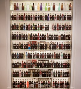 Wall of different Coca-Cola bottles in the Goizueta Foundation office
