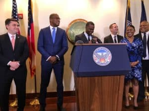 Atlanta Mayor Kasim Reed joyfully declares the city's $175 million in reserves as his CFO Jim Beard (in a blue suit) looks on (Photo by Maria Saporta)