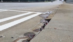 Rebar sticks up like teeth out of Capitol Avenue in Downtown where a curb cut belongs.