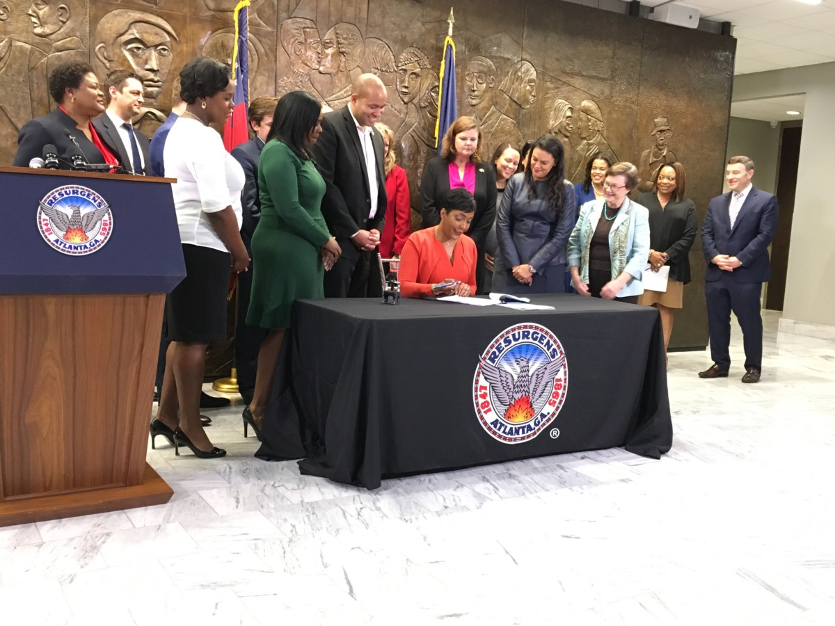 Atlanta Mayor Keisha Lance Bottoms signs an ordinance Tuesday to start transferring dozens of disputed property deeds to the city school system. School Superintendent Maria Carstarphen stands to Bottoms' left and other officials from the city and schools look on. Credit: Maggie Lee