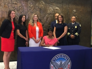 Atlanta Mayor Keisha Lance Bottoms, surrounded by staff and advocates on Thursday at City Hall, signs an executive order that will end a city jail contract provision with ICE. Credit: Maggie Lee
