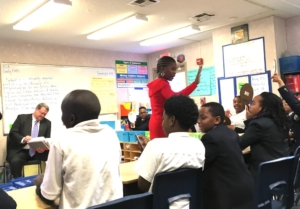 Atlanta Youth Academy fifth-grade teacher high-fives students after a mental math exercise on Wednesday, during a visit by the lieutenant governor. Credit: Maggie Lee