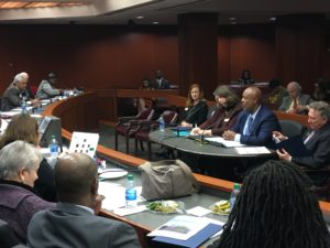 Dwight Robinson at a small table addresses state lawmakers at a large table
