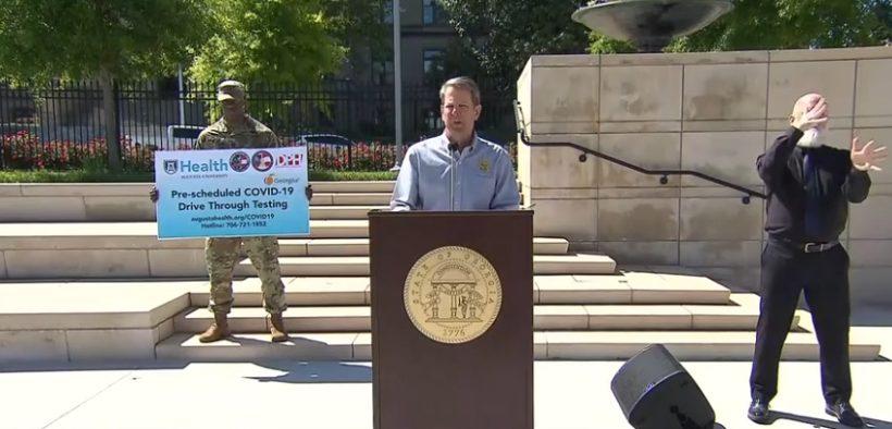 Brian Kemp at a podium outdoors