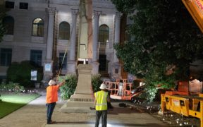 A machine lifts away a big monumental obelisk