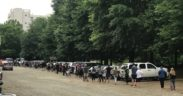 Dozens and dozens of people in a line in a parking lot