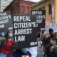 "Marchers in Atlanta carry signs reading ""Repeal Citizen's Arrest Law"""