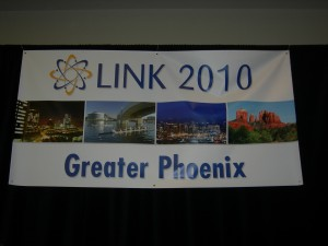 A picture of LINK banner hanging over group during closing exercises