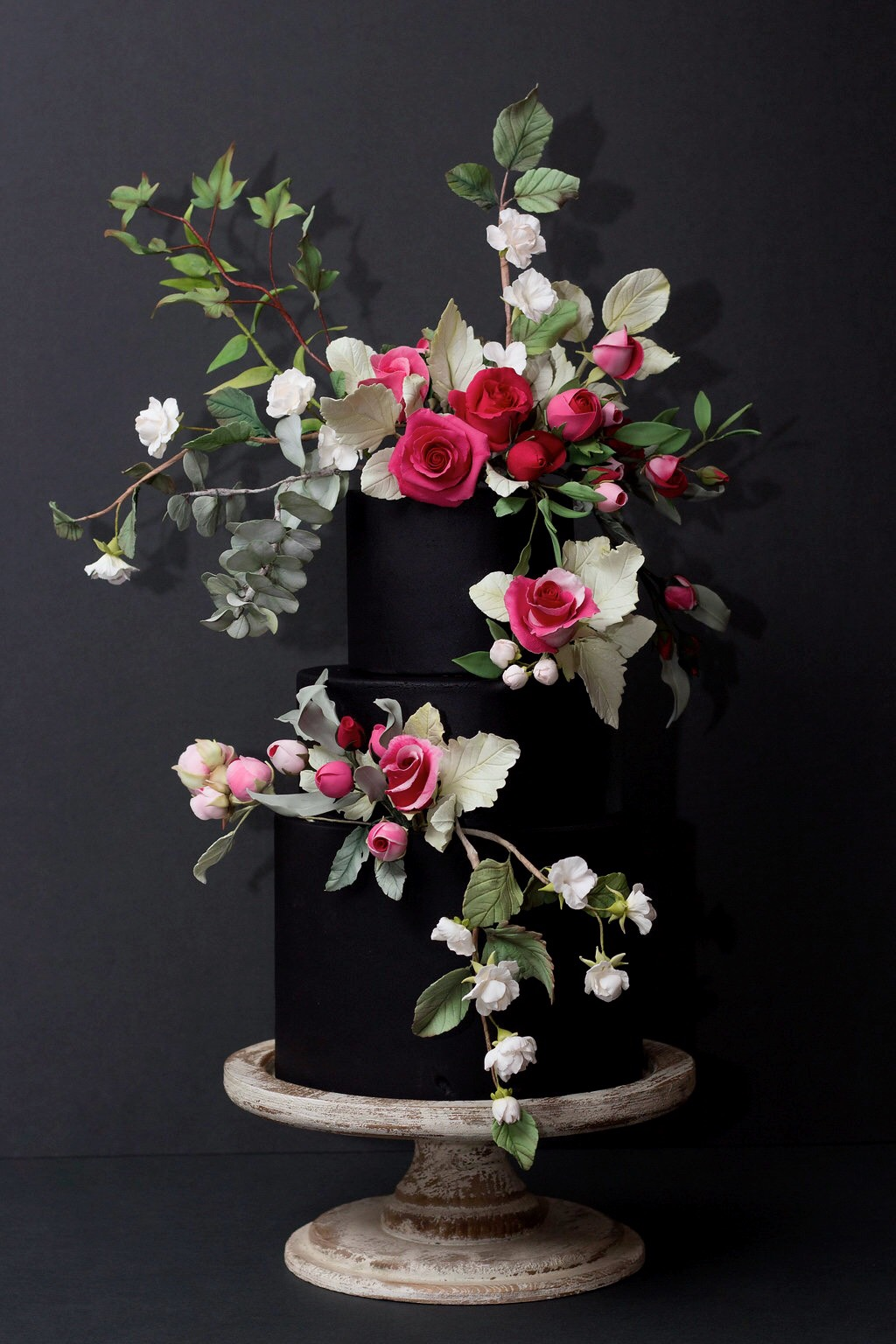 Black wedding cake with bouquet of sugar flowers