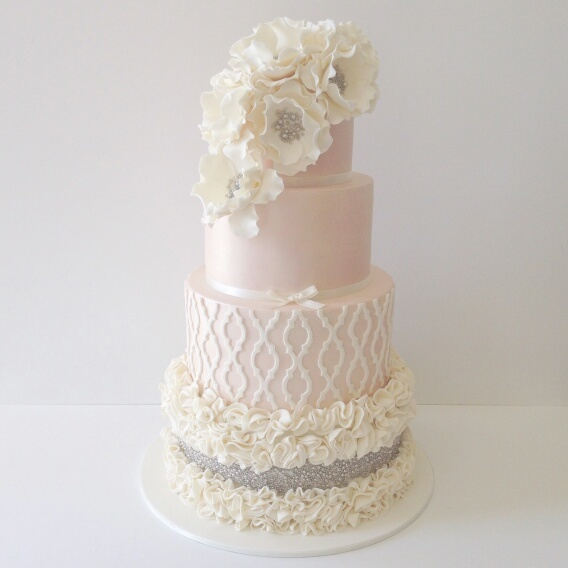 Pink and white ruffle wedding cake with white sugar flowers