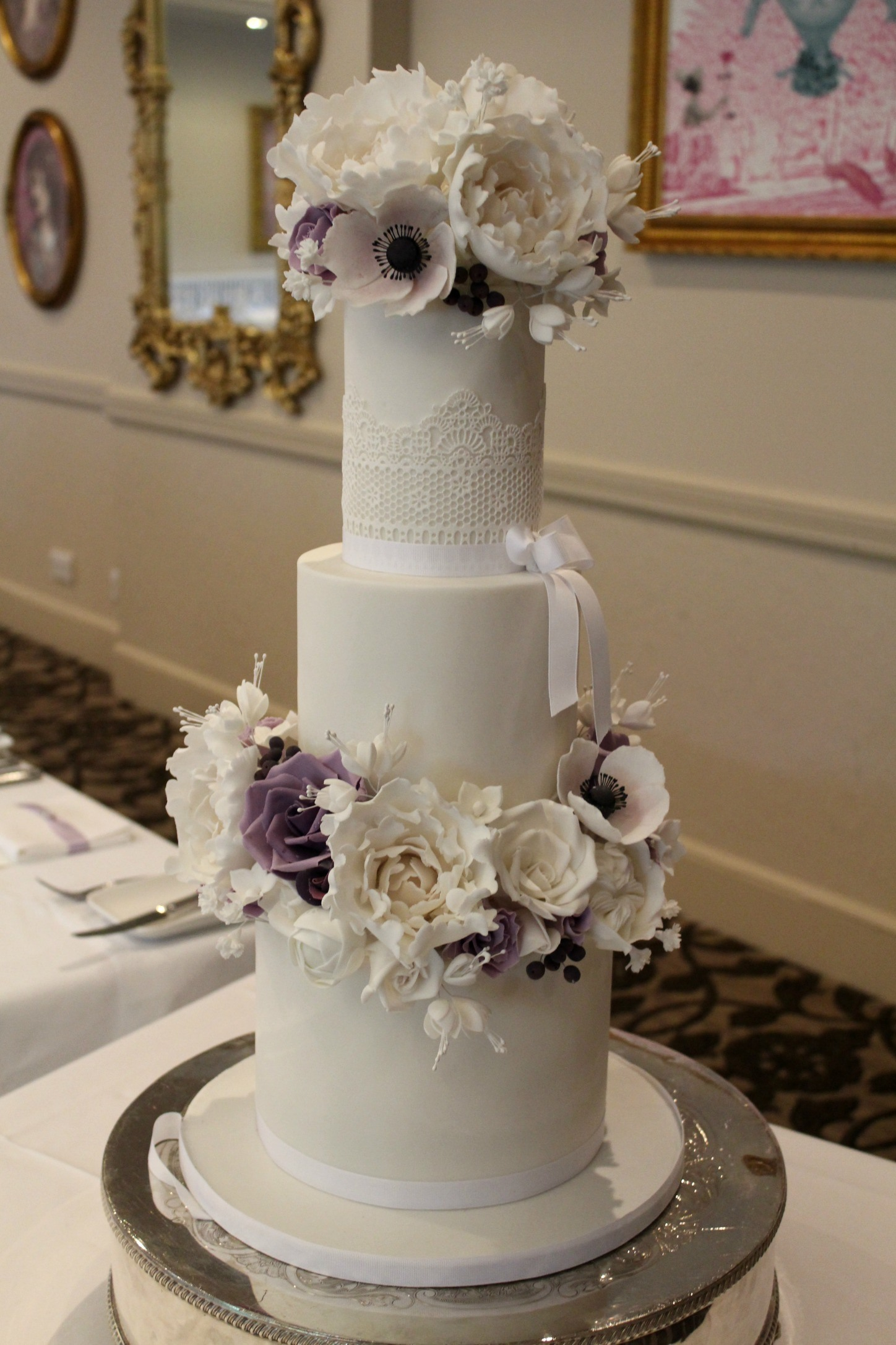 White wedding cake with lilac sugar flowers