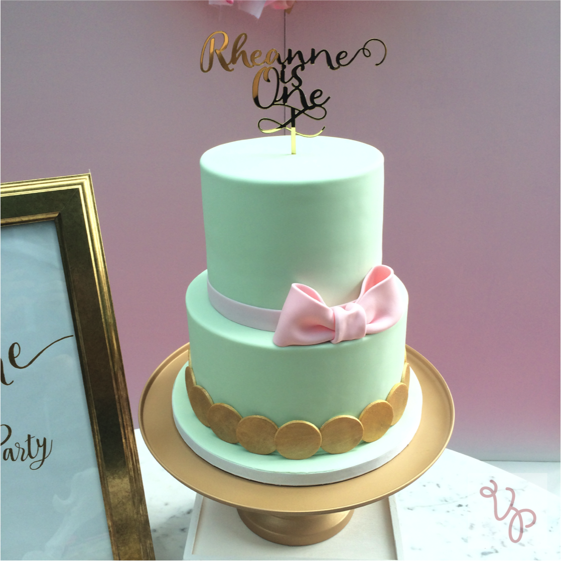 Pastel green birthday cake with pink sugar bow