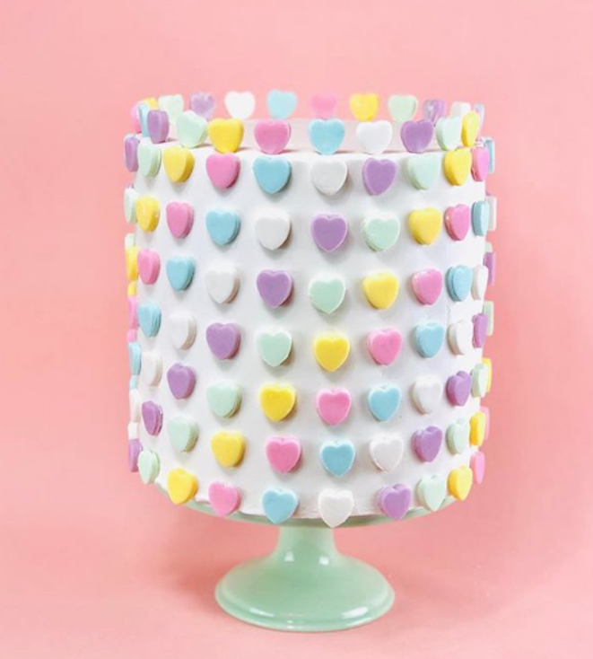 White fondant cake with pastel colored hearts