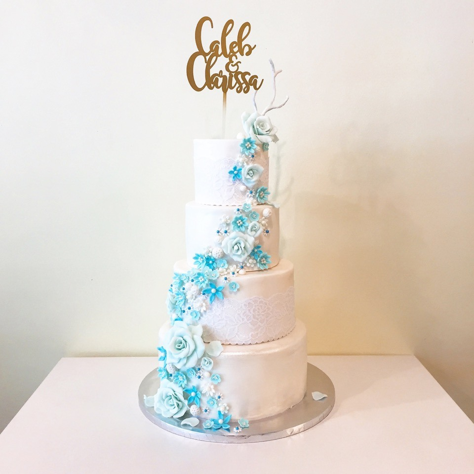 White wedding cake with cascading blue sugar flowers