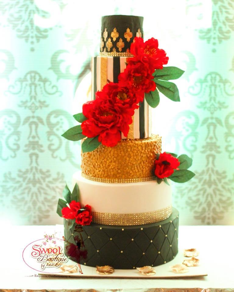Gold and black wedding cake with cascading red gum paste roses