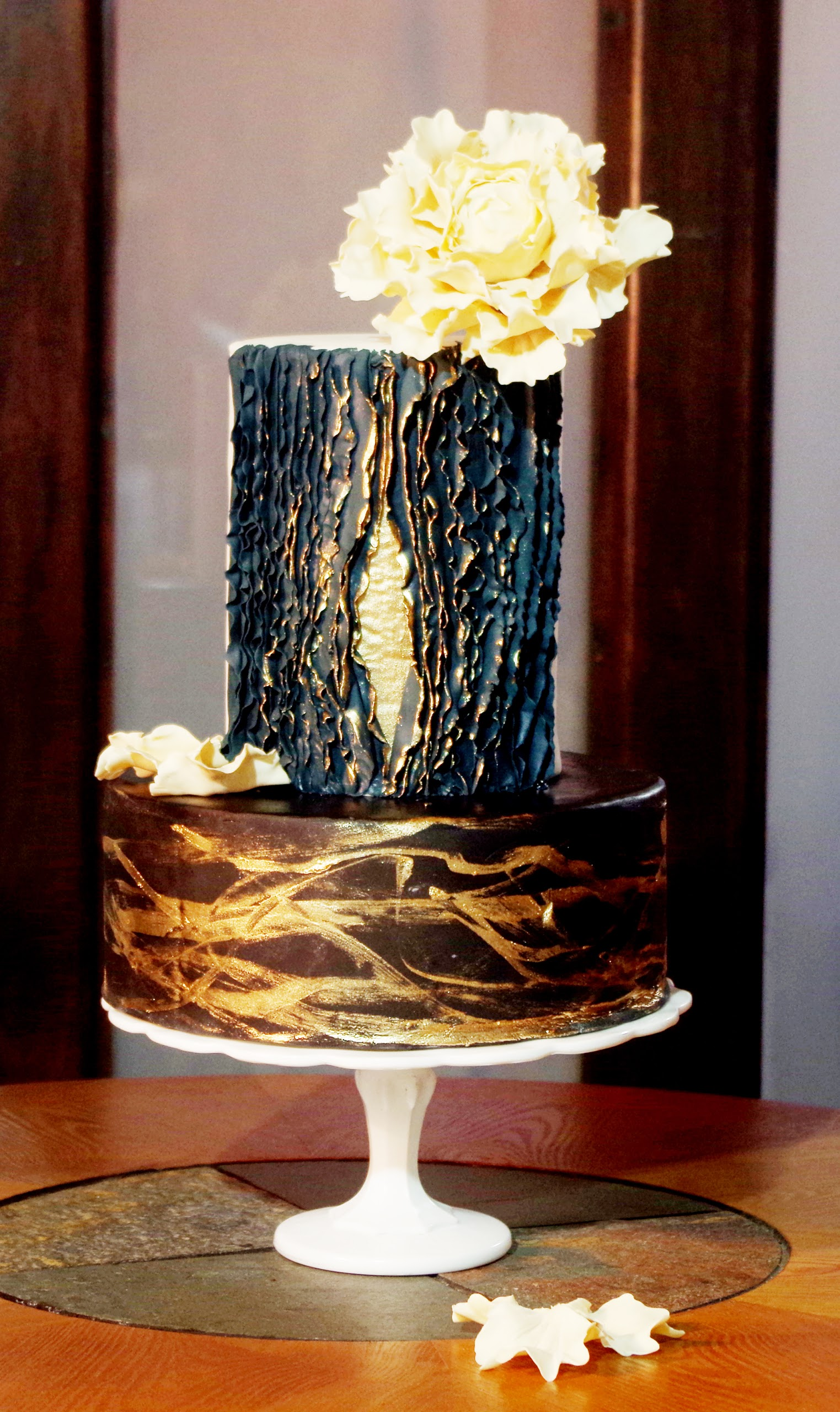 Black fondant wedding cake with gold trim ruffles