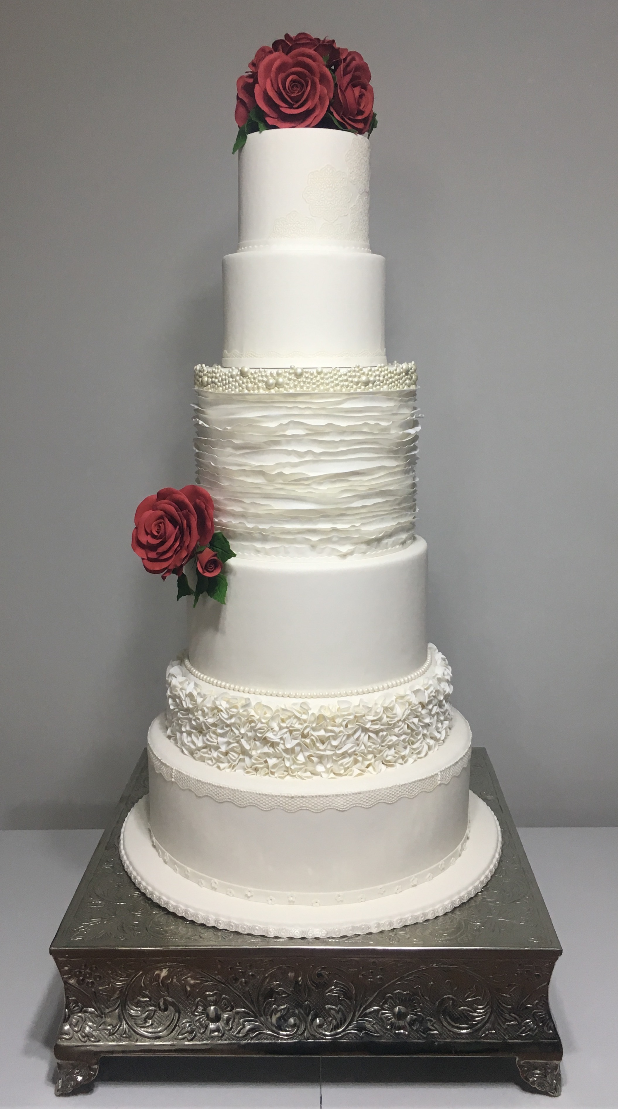 Tall white fondant wedding cake with red roses