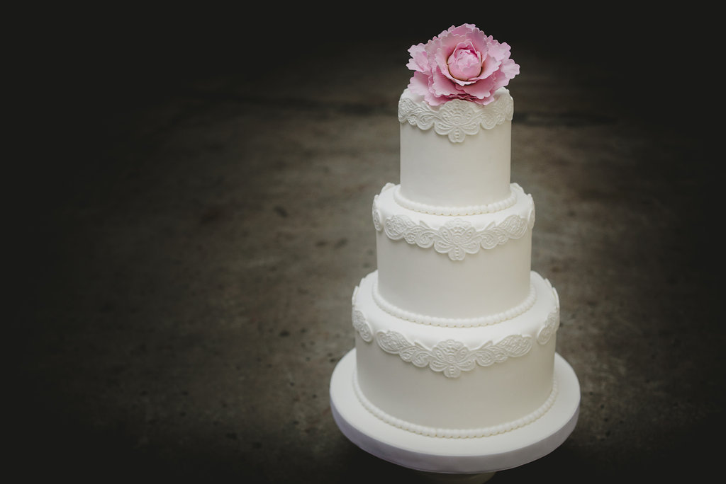 White fondant wedding cake with pink gum paste flower on top