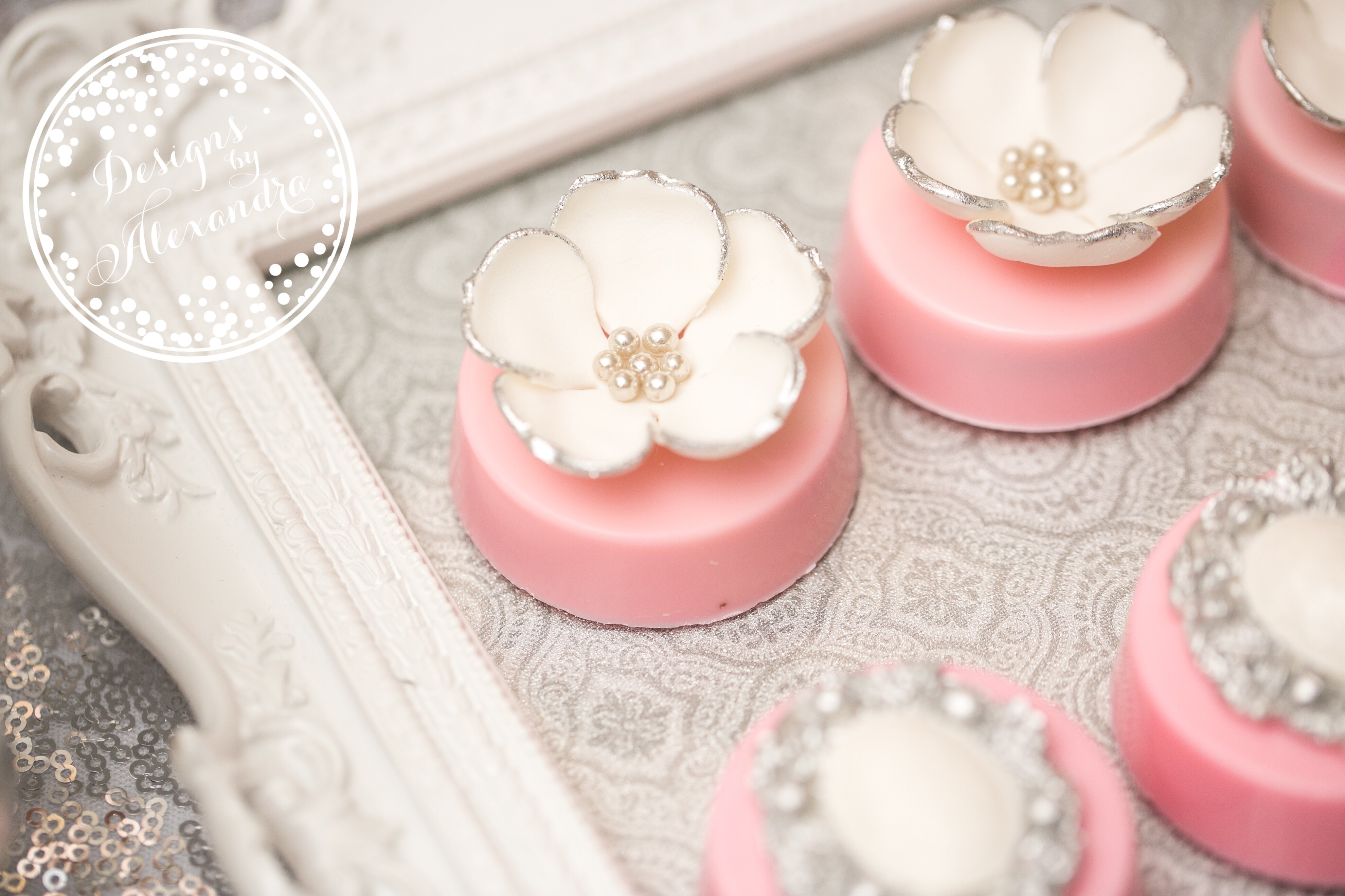 Pink mini cakes with white sugar flowers