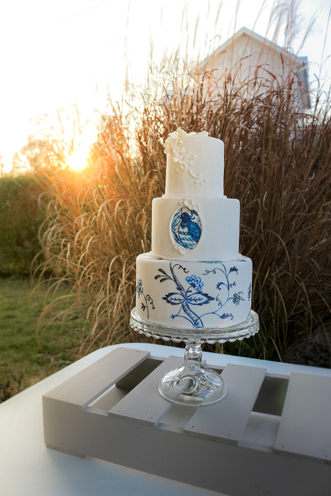 Artistic wedding cake with hand painted blue flowersa