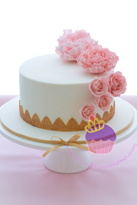 Mini white cake with gold trim and pink sugar flowers