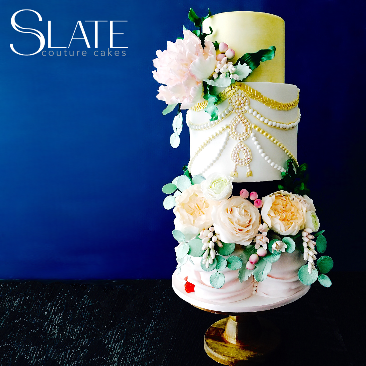 Yellow white and light pink art deco themed wedding cake with sugar flowers