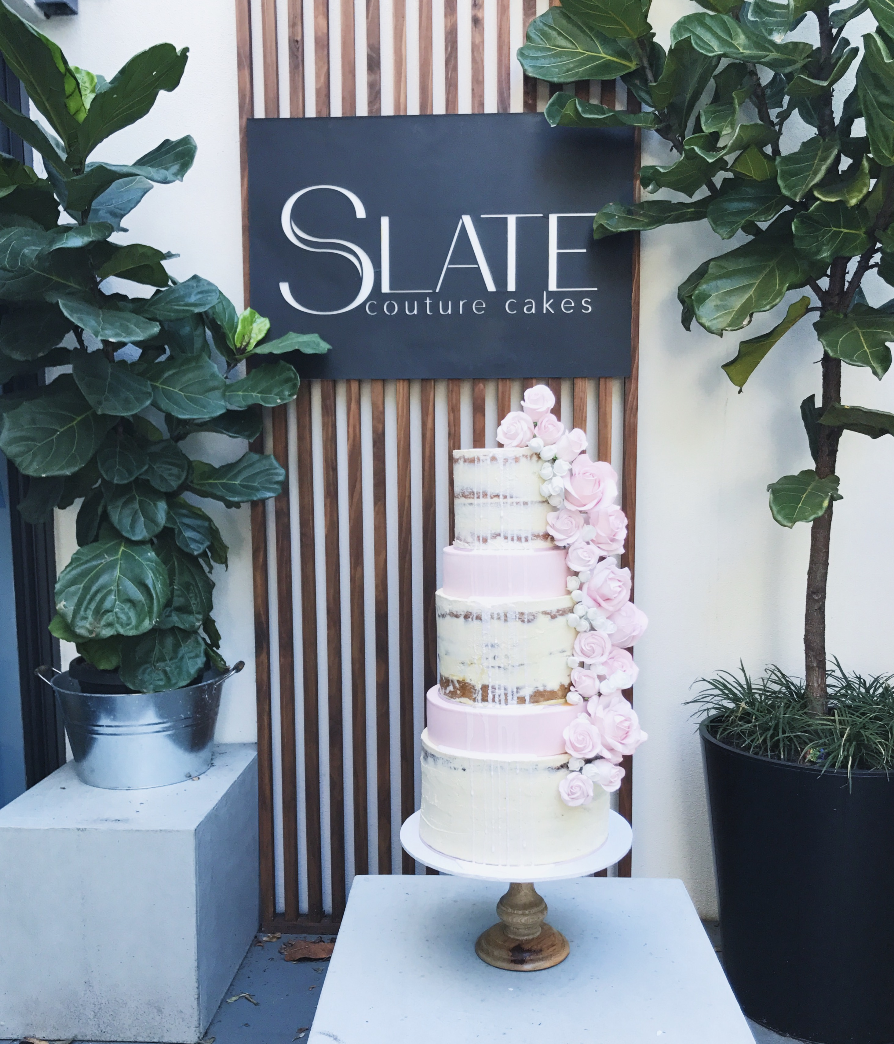 White and pink naked cake with pink sugar flowers