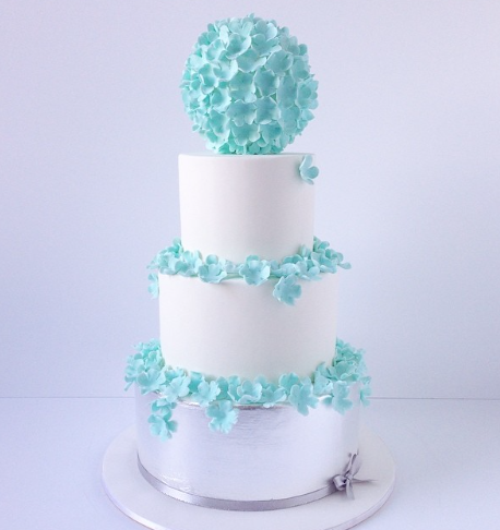 White fondant wedding cake with turquoise sugar flowers