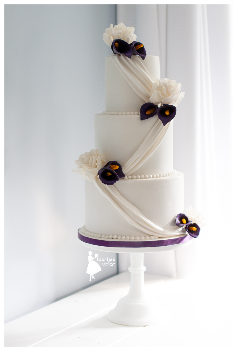 White wedding cake with navy sugar flowers