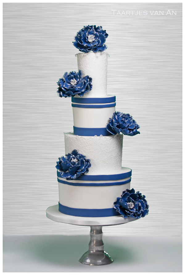 White fondant wedding cake with blue sugar flowers