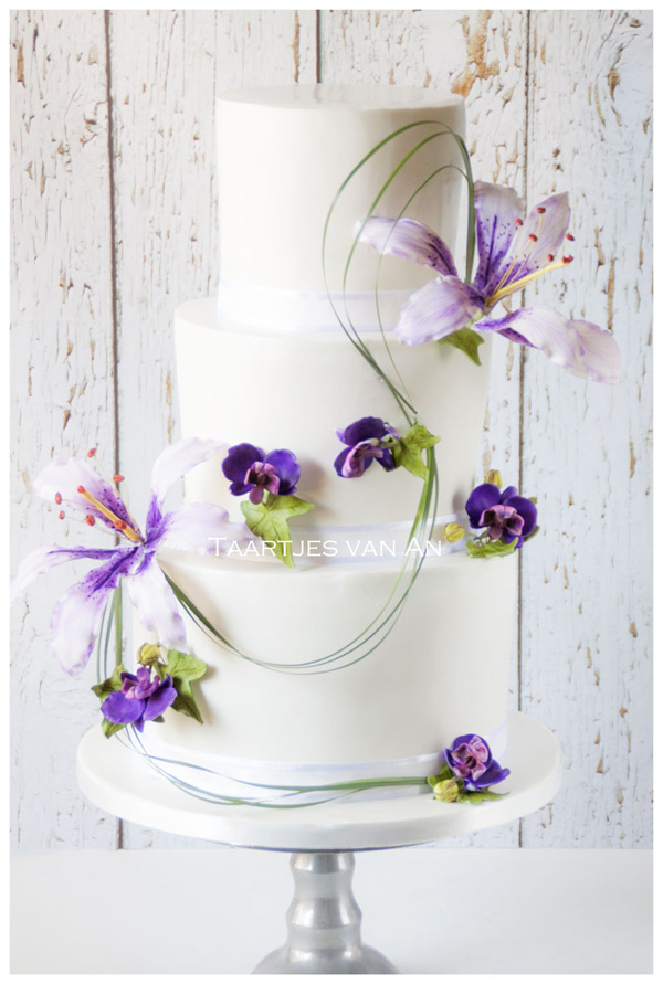 White fondant wedding cake with lavender sugar flowers