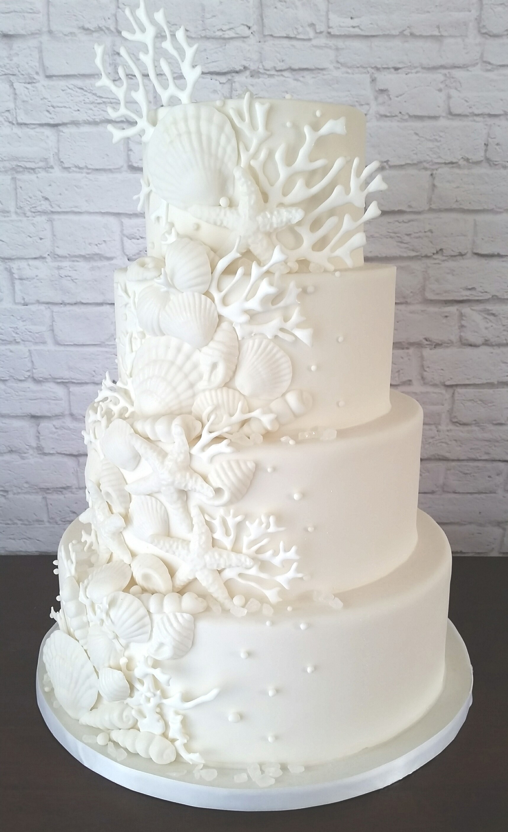 All white fondant wedding cake with seashells