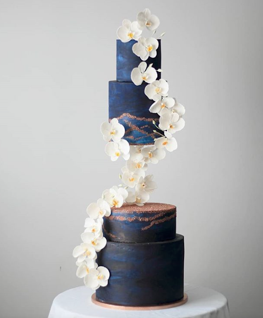 Modern navy blue fondant wedding cake with cascading white sugar flowers