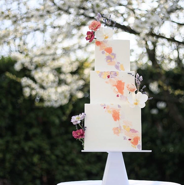 White fondant wedding cake with orange painted flowers