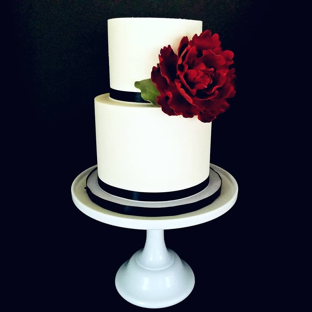 White fondant wedding cake with red sugar rose
