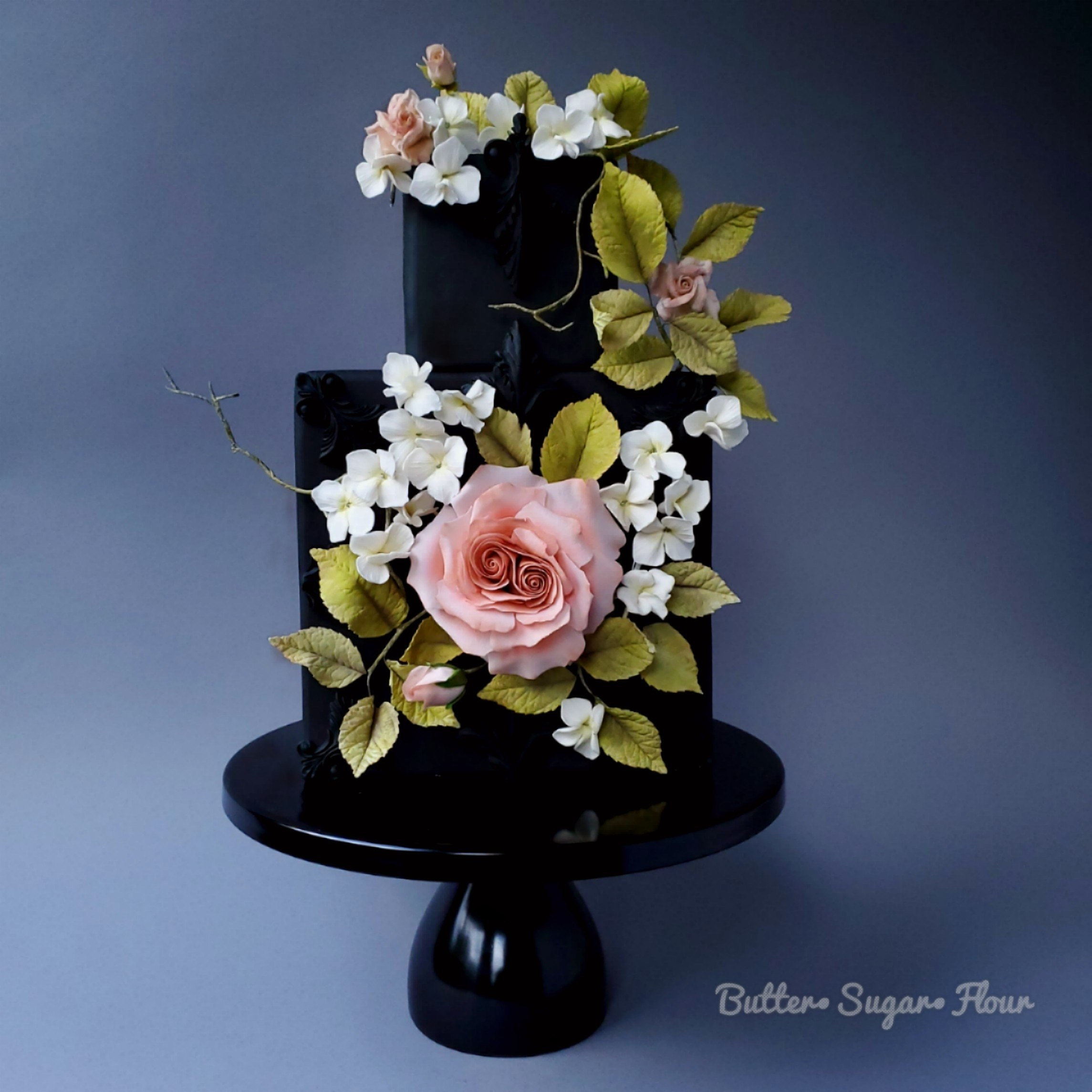 All black fondant cake covered with blush sugar flowers