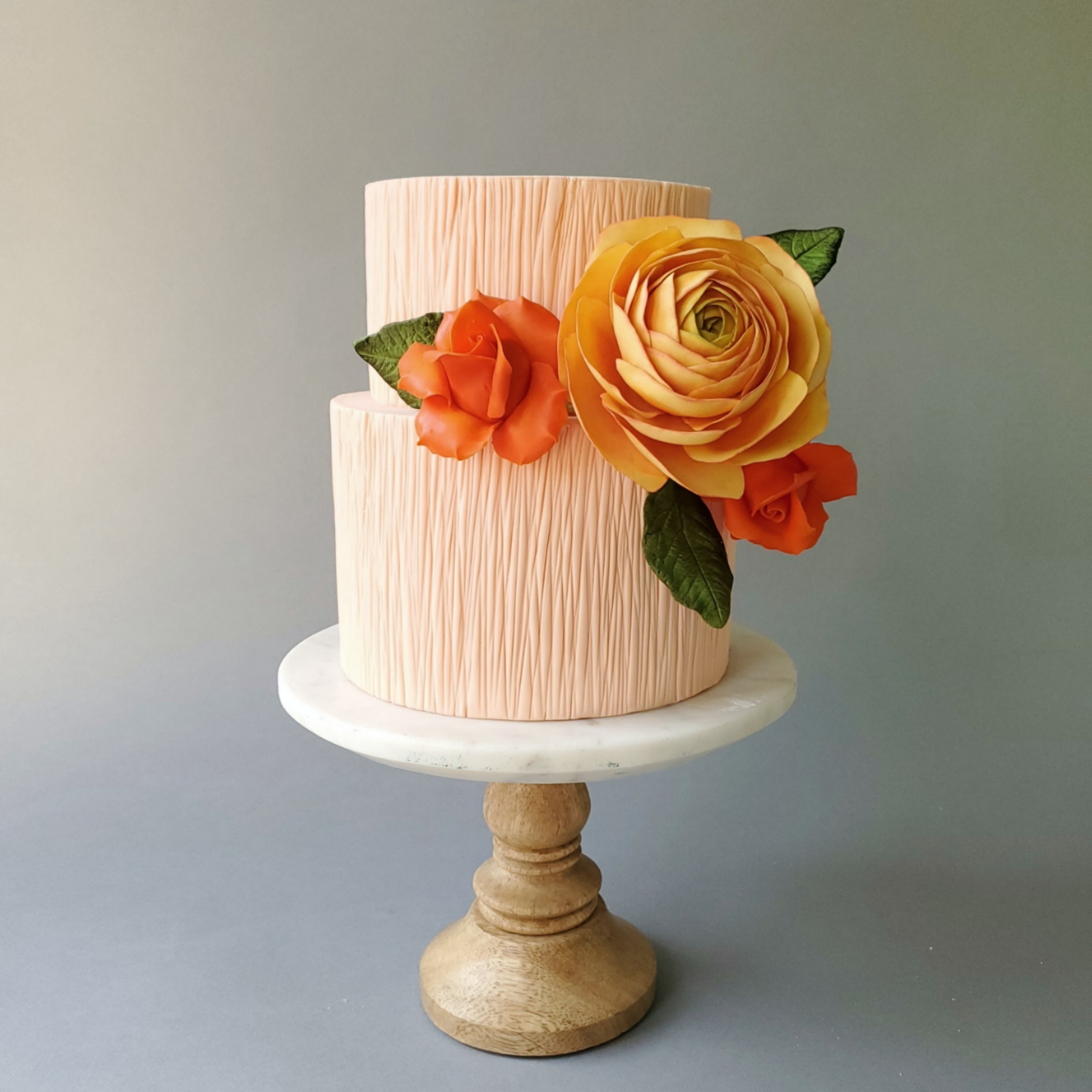 All peach wedding cake with citrus floral bouquet