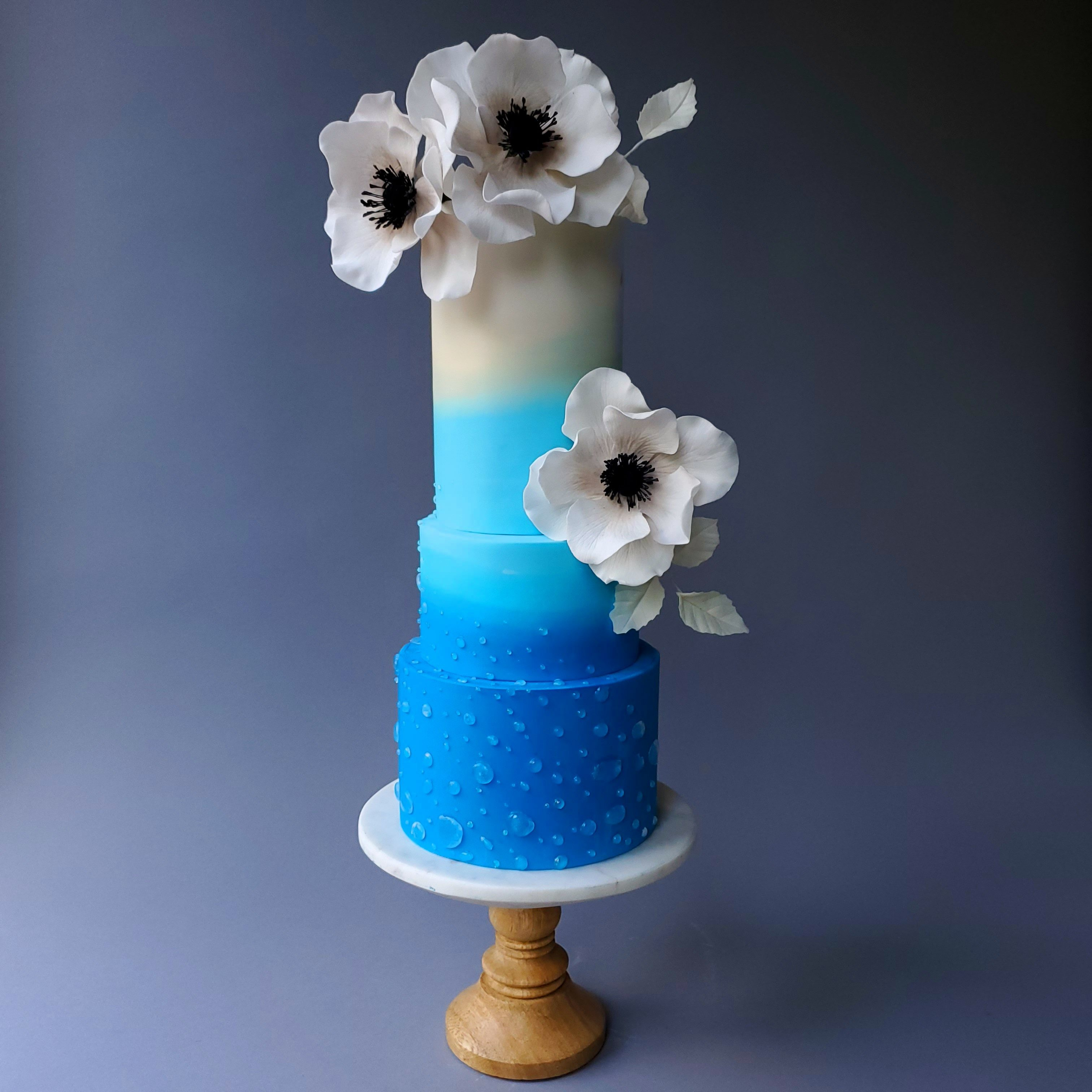 Blue on blue fondant wedding cake with white sugar flowers
