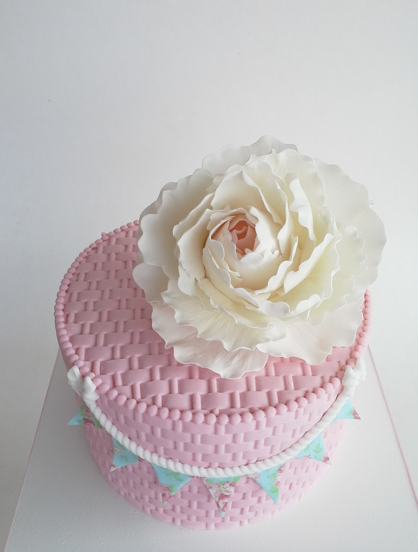 Mini pink birthday cake with white sugar flower