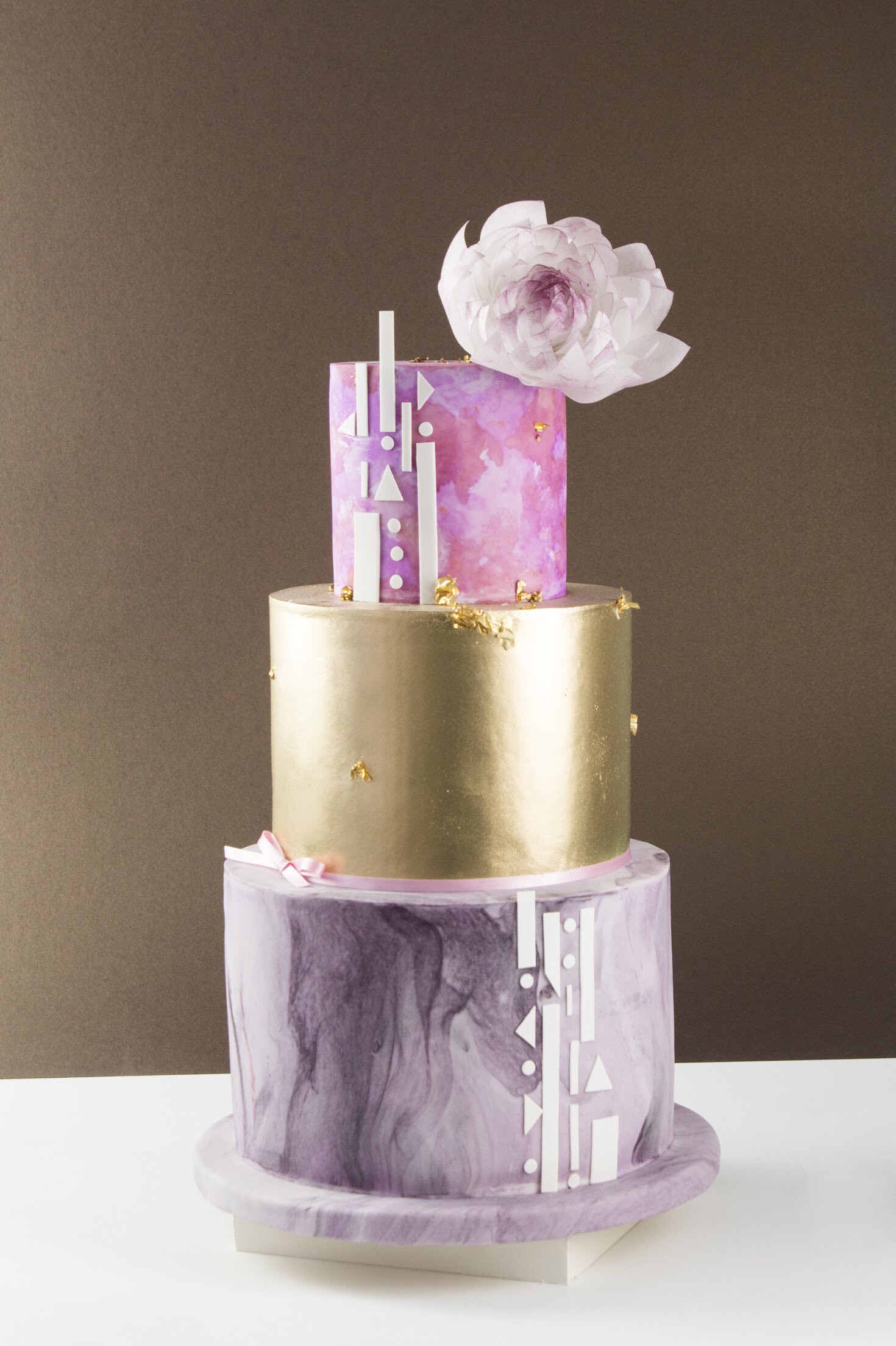 Purple and pink wedding cake with a gold tier