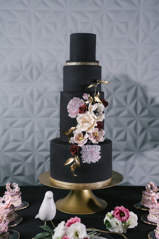 Black fondant wedding cake with purple hued sugar flowers