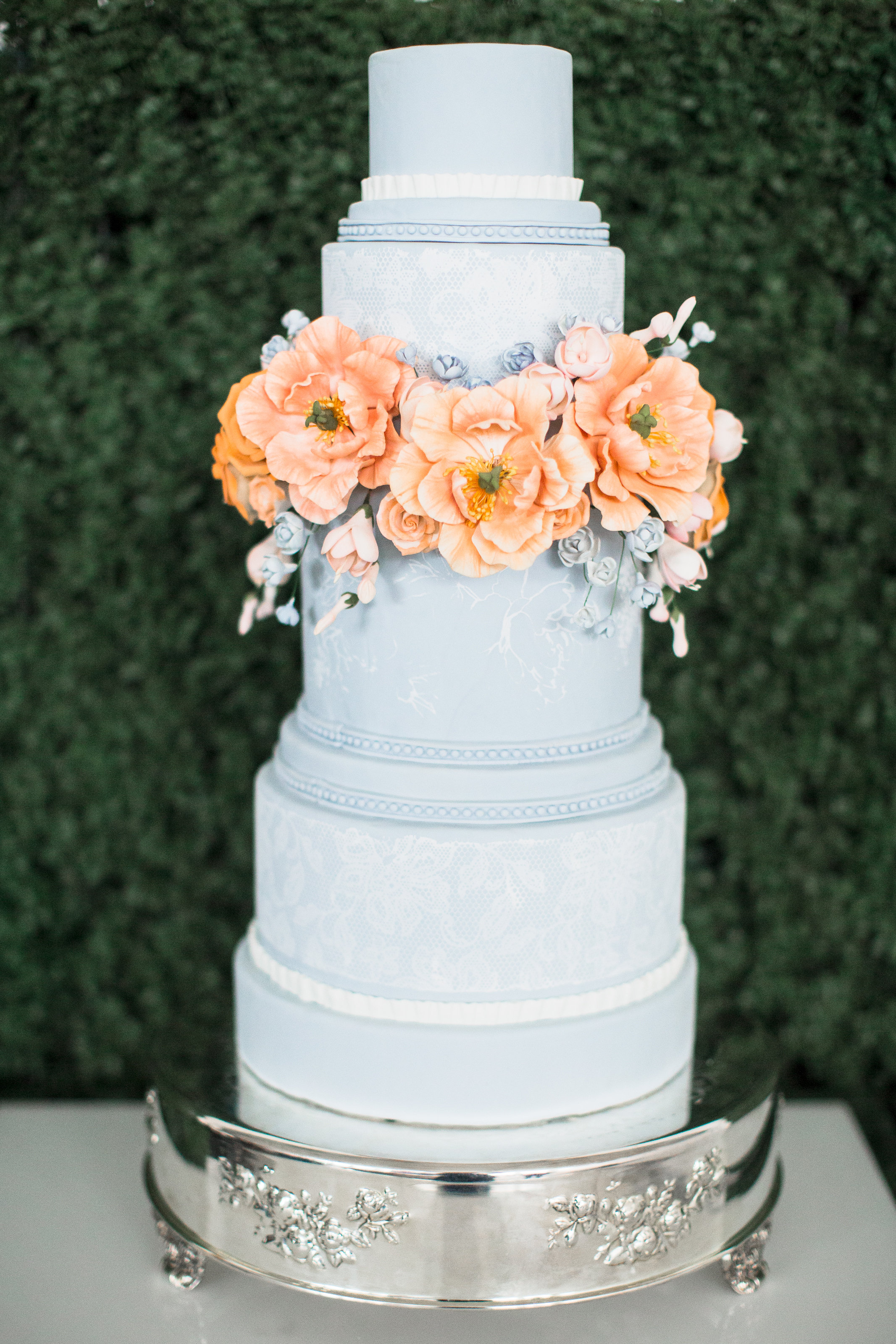 Baby  blue wedding cake with orange sugar flower wreath