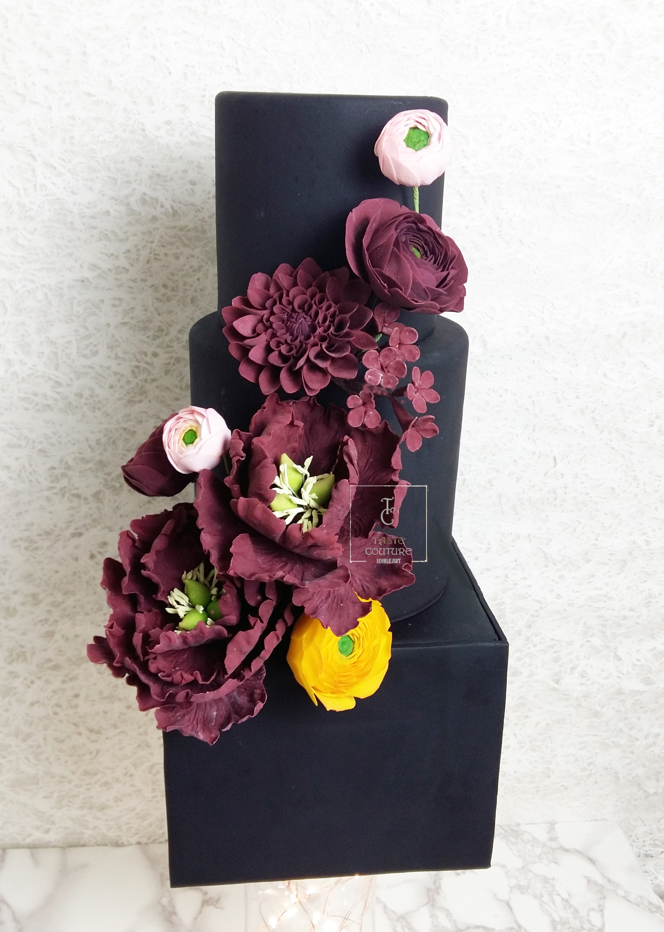 Black fondant wedding cake with burgundy flowers