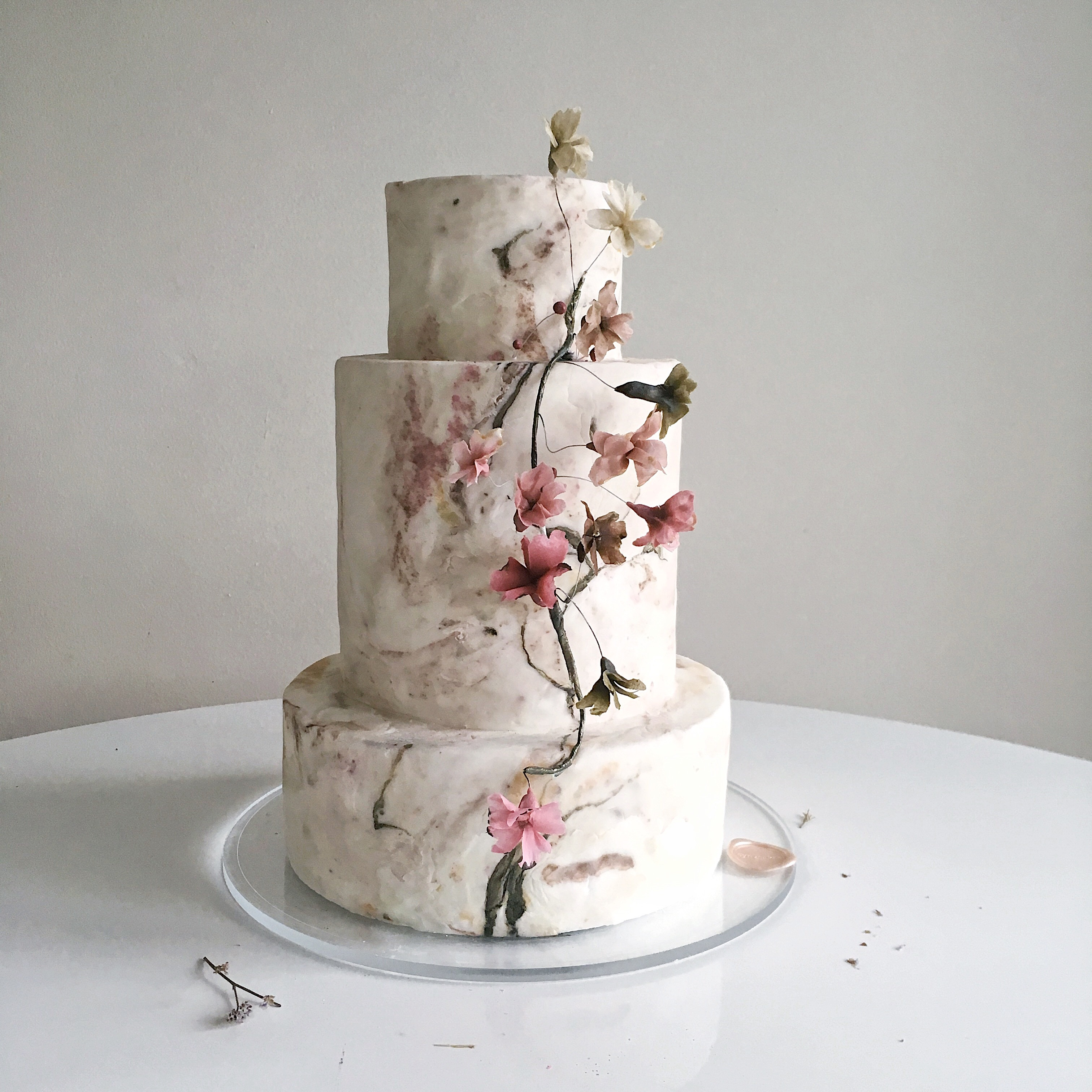 Textured ivory wedding cake with cherry blossoms